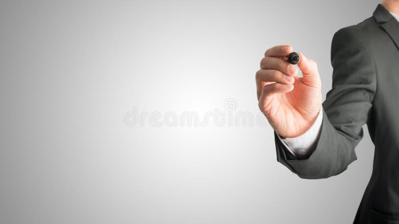 Closeup av den manliga handen som omkring rymmer en svart markör för att skriva somet royaltyfri bild