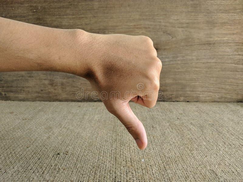 Closeup av den manliga handen som visar tummar ner tecken arkivbild