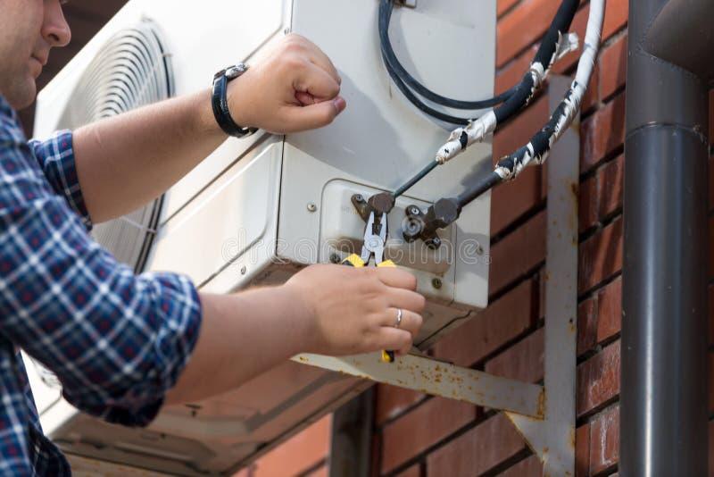 Closeup av den manliga teknikeren som uni reparerar den utomhus- luftkonditioneringsapparaten arkivfoto
