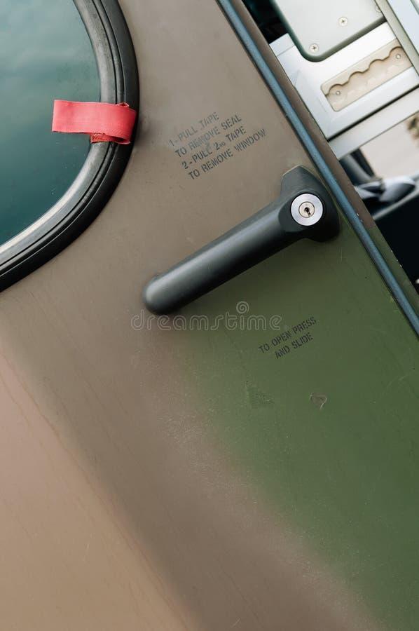 Closeup av den militära helikopterdörren med handtaget och handstilar arkivbild
