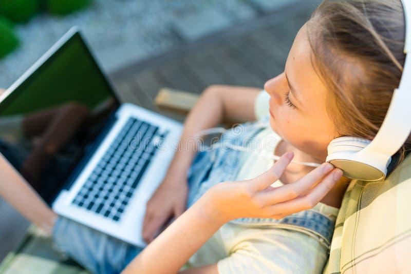 Closeup av den nätta tonåriga flickan i hörlurar som lyssnar till musikusien arkivbilder