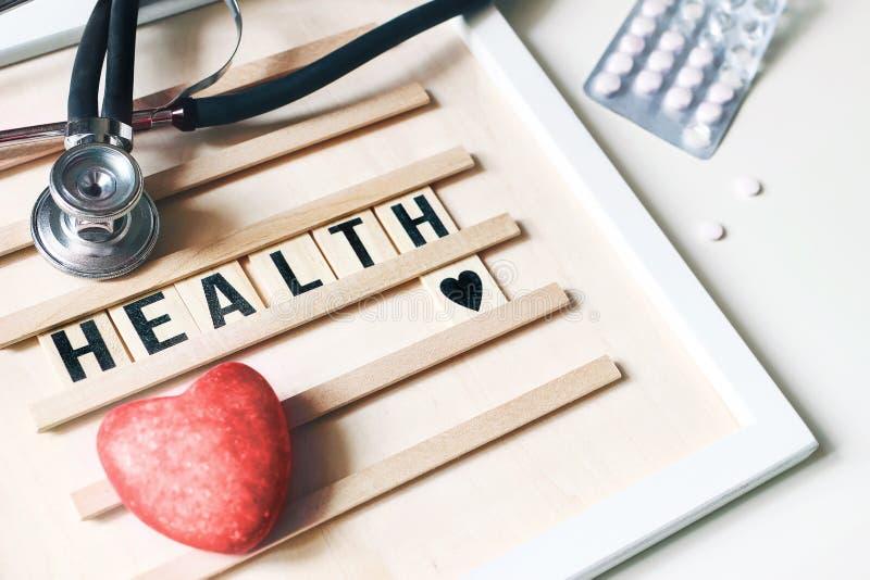 Closeup av den röda hjärtastenen, stetoskopet, träbokstavsbrädet och piller på vit tabellbakgrund Hälsovård läkarundersökning royaltyfri bild