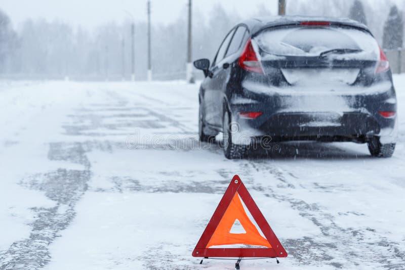 Closeup av den röda varningstriangeln med en bruten ner bil i vinter arkivfoto