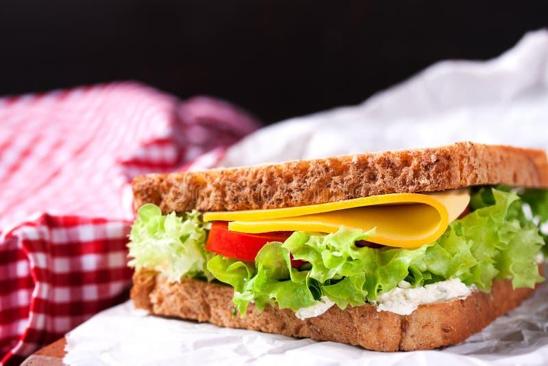 Closeup av den rostade smörgåsen med salladsidor, tomater och ost med gaffeln på en skärbräda på en mörk bakgrund royaltyfri foto