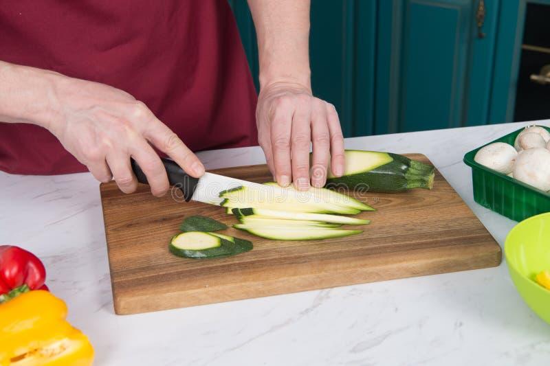 Closeup av den skivade zucchinin på tabellen Slut upp av händer som skivar den gröna grönsaken med den vita kniven Closeup av män royaltyfria foton