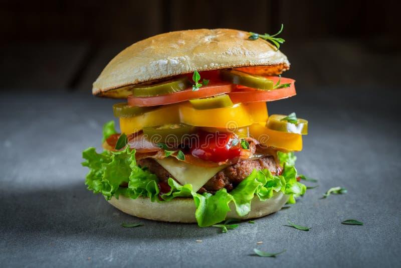 Closeup av den smakliga hamburgaren med nötkött, ost och grönsaker royaltyfria bilder