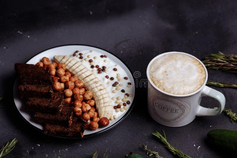 Closeup av den sunda frukostplattan med yoghurt, bananen, rågbröd, hasselnöten, en kopp av latte eller kaffe, kakao på ett svart  royaltyfri fotografi