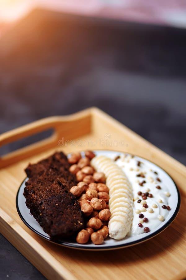 Closeup av den sunda frukostplattan med yoghurt med chokladchiper, bananen, rågbröd och hasselnöten royaltyfri bild