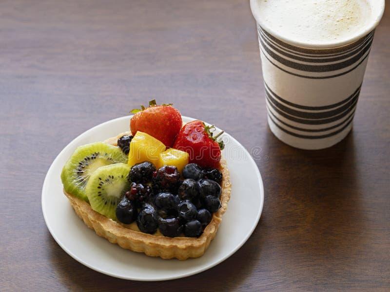 Closeup av den syrliga efterrätten för frukt med jordgubbar, kiwin, ostkräm och varmt svart kaffe royaltyfria bilder