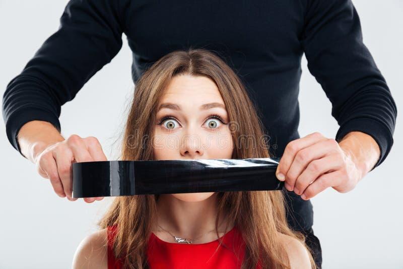 Closeup av den täckande kvinnamunnen för man vid det svarta bandet arkivfoton