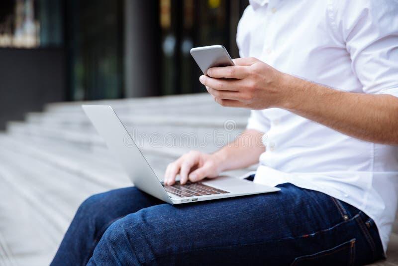 Closeup av den unga affärsmannen som utomhus använder bärbara datorn och mobiltelefonen royaltyfri fotografi