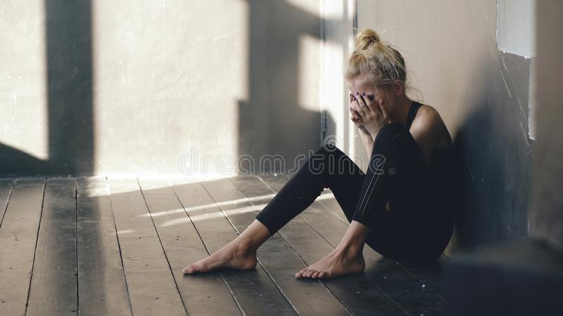 Closeup av den unga dansaregråt för tonårs- flicka, efter förlustkapaciteten har suttit på golv i korridor inomhus royaltyfri foto