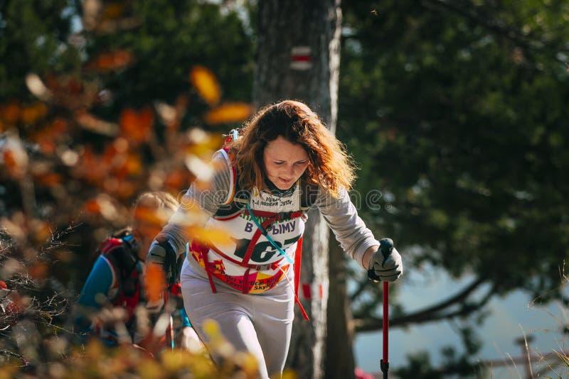 Closeup av den unga kvinnan med att fotvandra pinnar Hösten landskap arkivfoton