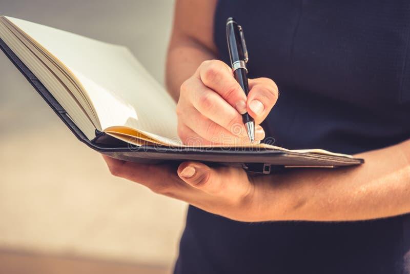 Closeup av den unga kvinnan som ner skrivar brev i notepaden för makin royaltyfri fotografi