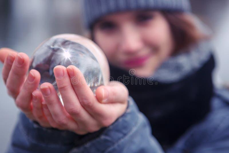 Closeup av den unga kvinnan som rymmer en glass sfär royaltyfri foto