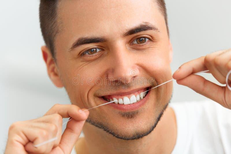 Closeup av den unga mannen som flossing hans tänder Lokalvårdtänder med hålan royaltyfria bilder