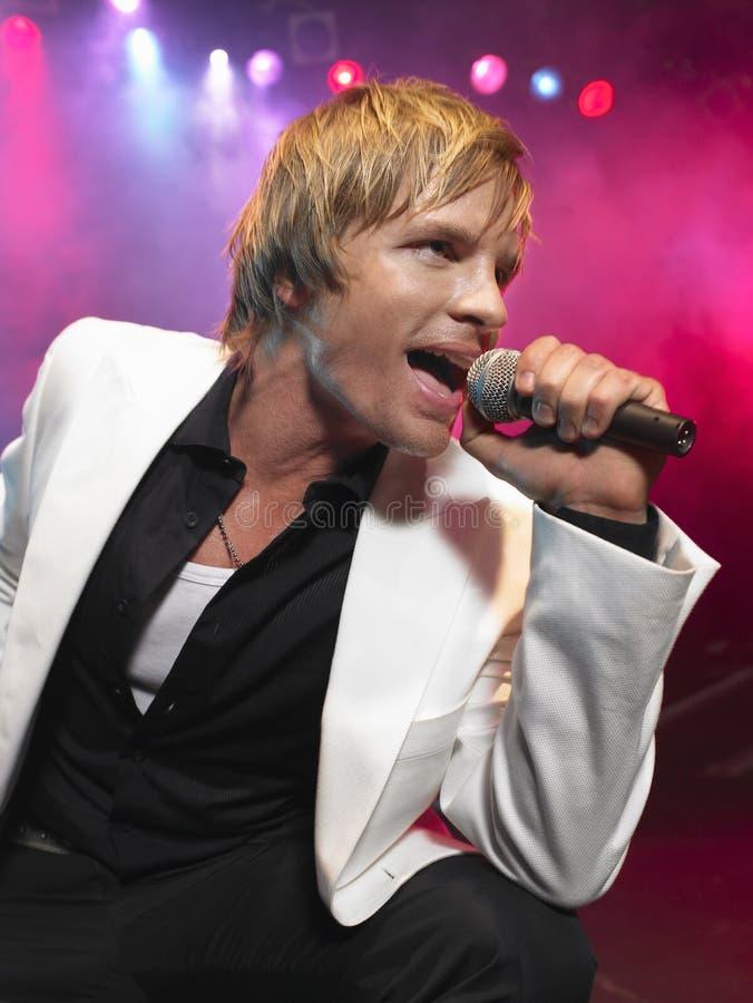 Closeup av den unga mannen som sjunger in i mikrofonen royaltyfria bilder