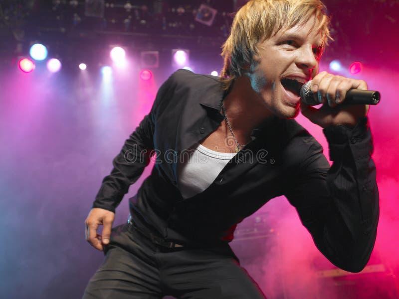 Closeup av den unga mannen som sjunger in i mikrofonen fotografering för bildbyråer