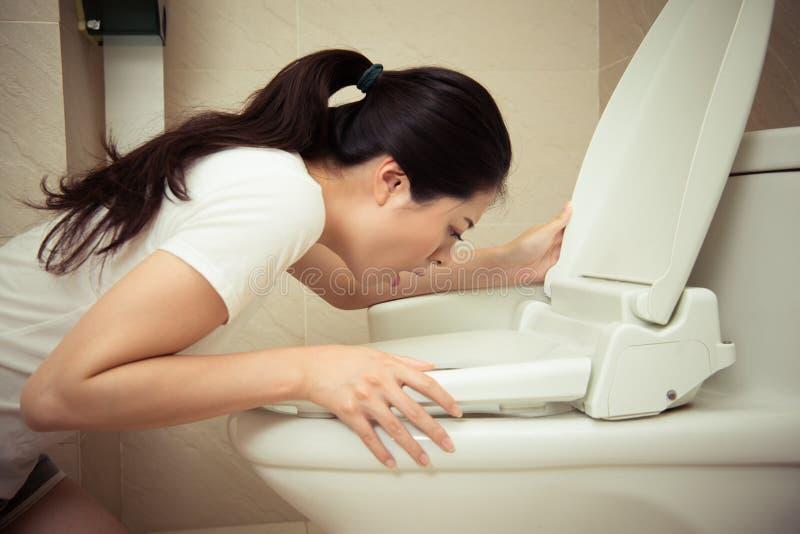 Closeup av den unga nätta kvinnan som spyr in i toalett arkivbilder