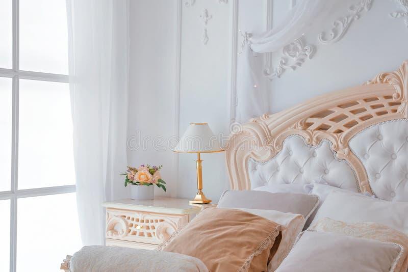 Closeup av det ljusa vita sovrummet som är inre med natttabelllampan och fönstret royaltyfri fotografi