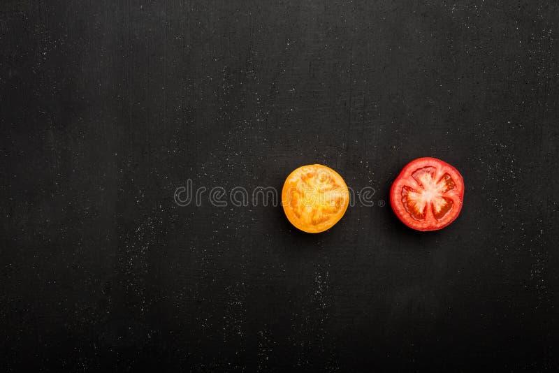Closeup av det mogna saftiga röda och orange tomatsnittet i halva med på en stentabell arkivfoto