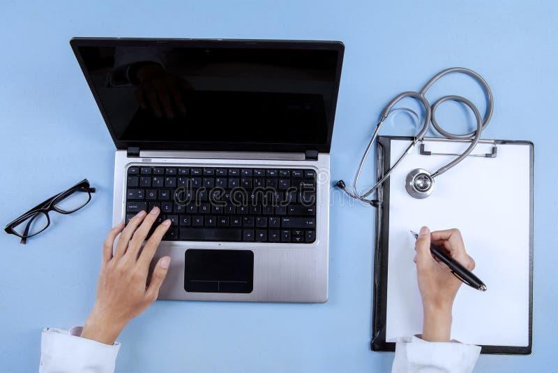 Closeup av doktorshänder genom att använda bärbara datorn royaltyfri bild
