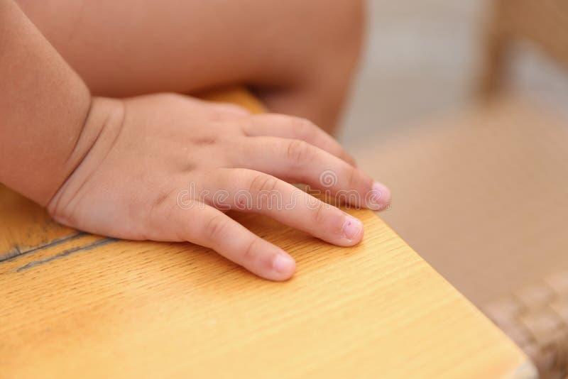 Closeup av en child& x27; s-handsammanträde på ett skrivbord, royaltyfri foto