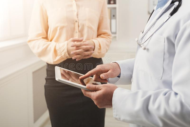 Closeup av en doktor som pekar in i minnestavlan och patient arkivbilder