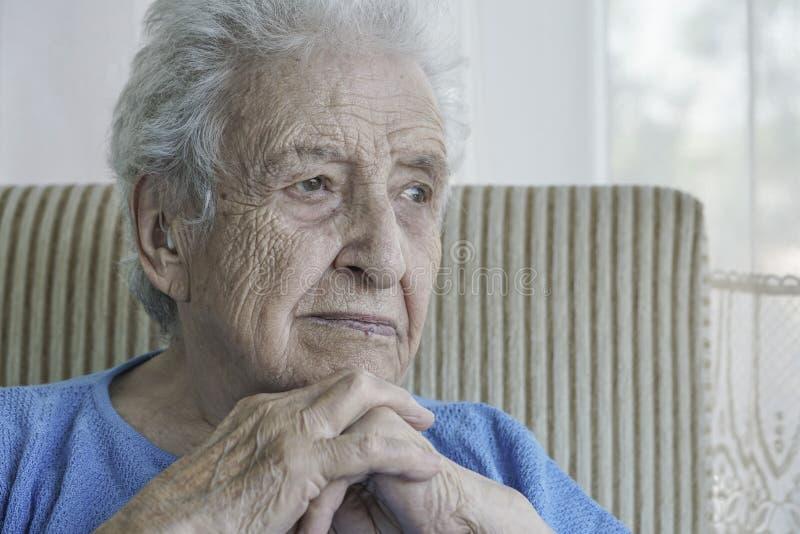 Closeup av en fundersam gammal kvinna hemma royaltyfri foto