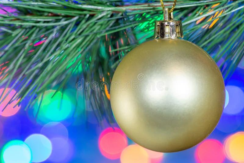Closeup av en guld- boll för härlig julgrangarneringleksak på bakgrunden av den oskarpa ljusgirlanden royaltyfri bild