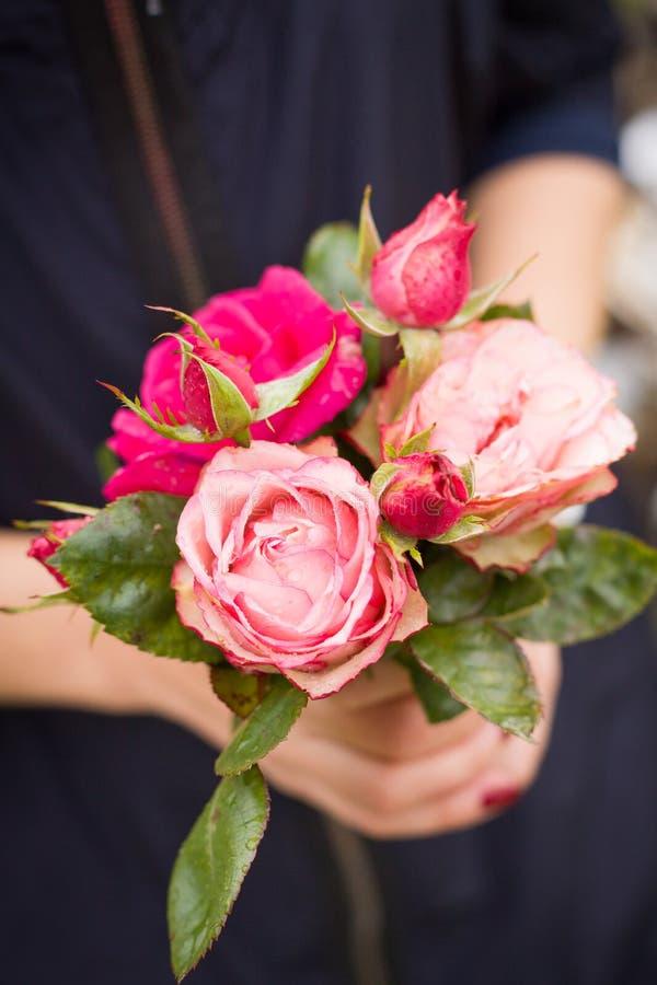 Closeup av en härlig bukett av rosa rosor i händer för kvinna` s Stranda av hår vänder mot in Nya blommor som en gåva från en trä royaltyfri bild