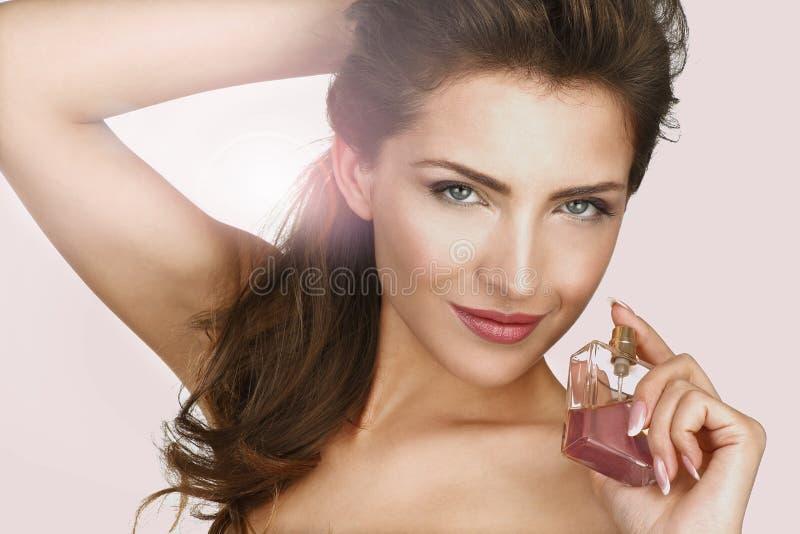 Closeup av en härlig kvinna som applicerar doft arkivbilder