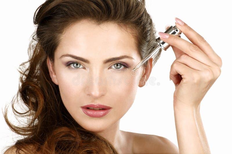 Closeup av en härlig kvinna som applicerar en skönhetbehandling royaltyfria bilder