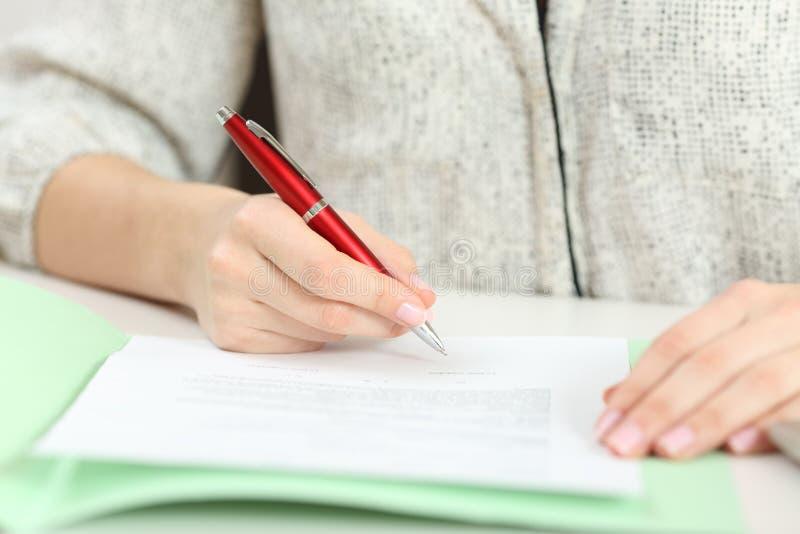 Closeup av en hand som undertecknar ett avtal på ett skrivbord royaltyfri bild