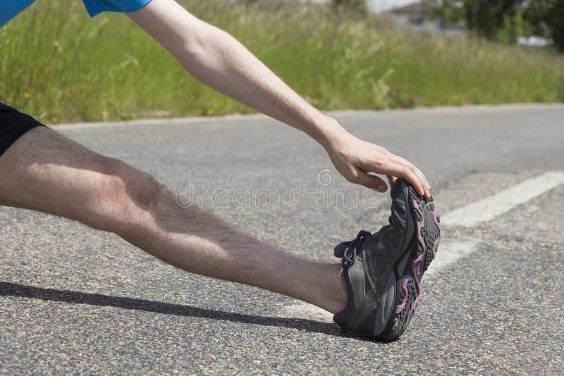 Closeup av en jogger som sträcker hans ben royaltyfria foton
