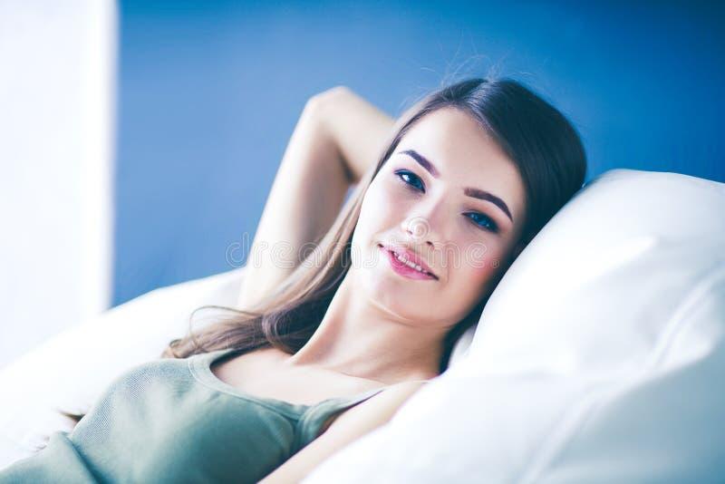 Closeup av en le ung kvinna som ligger på soffan arkivbild