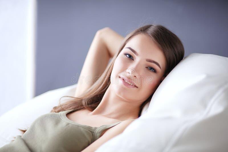 Closeup av en le ung kvinna som ligger på soffan royaltyfria foton