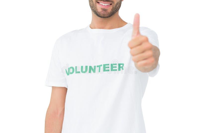 Closeup av en lycklig manlig volontär som gör en gest upp tummar royaltyfria bilder