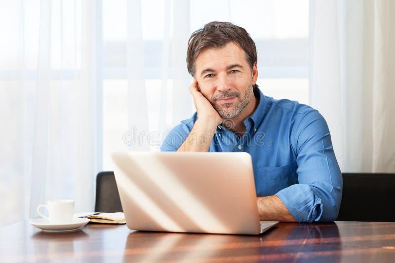 Closeup av en medelålders man som borras på en gardinbakgrund på kontoret royaltyfria bilder