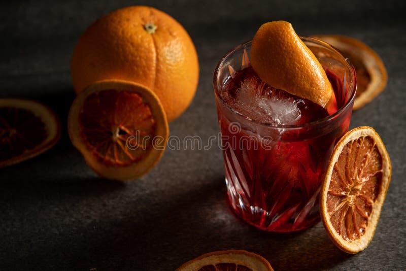 Closeup av en röd coctail i ett exponeringsglas med en orange skiva och en apelsin i bakgrunden royaltyfria bilder