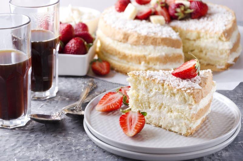 Closeup av en skiva av sockerkakan på plattan, exponeringsglas av kaffe, bunke av jordgubbar, hel sockerkaka på bakgrunden royaltyfria foton