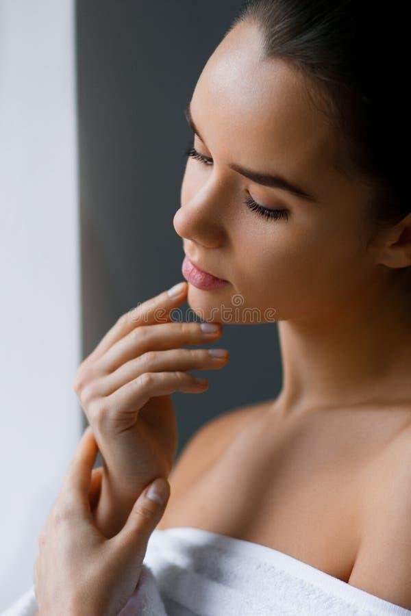 Closeup av en ung härlig kvinna med näck makeup som trycker på hennes framsida Skönhet brunnsort royaltyfri fotografi