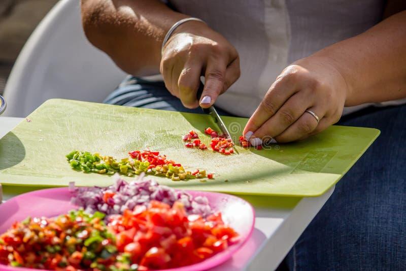 Closeup av en vuxen kvinnligs händer som klipper grönsaker arkivfoto