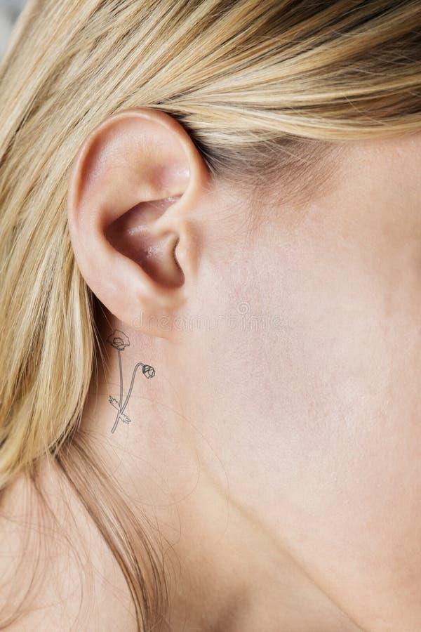 Closeup av ett enkelt bak öratatueringen av en ung kvinna royaltyfri foto