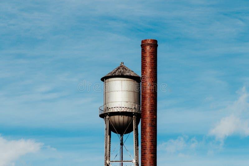 Closeup av ett högväxt vattentorn med ett stort rör för metall bredvid det fotografering för bildbyråer