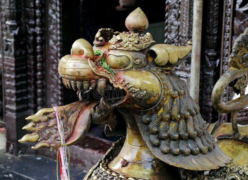 Closeup av ett metalliskt lejon som bevakar templet i det mitt- av Phewa sjön arkivbilder