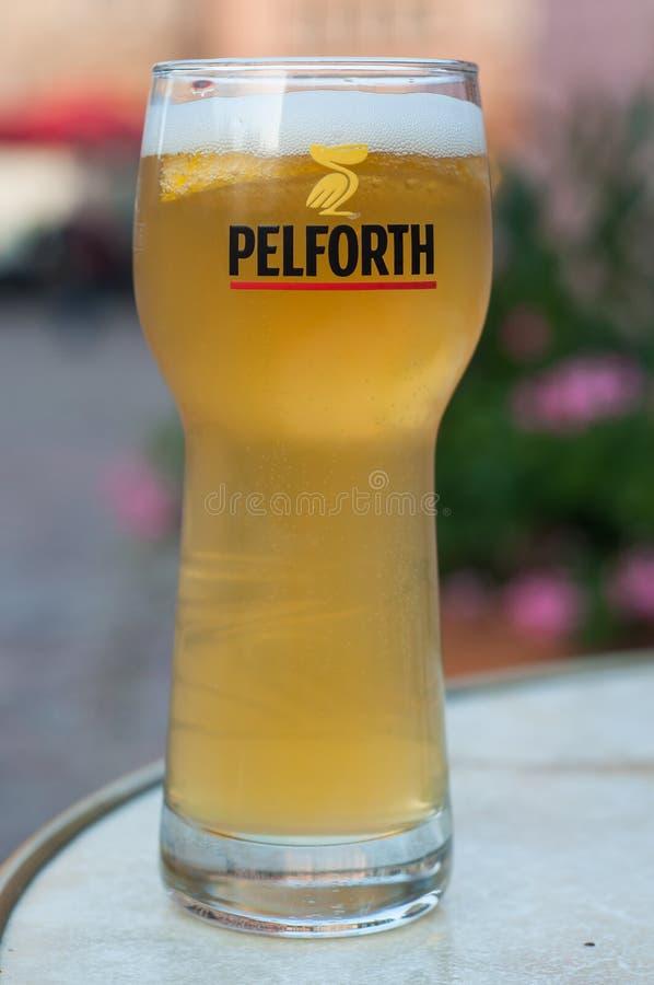 Closeup av exponeringsglas av franskt öl från det Pelfort märket på restaurangterrassen royaltyfri bild