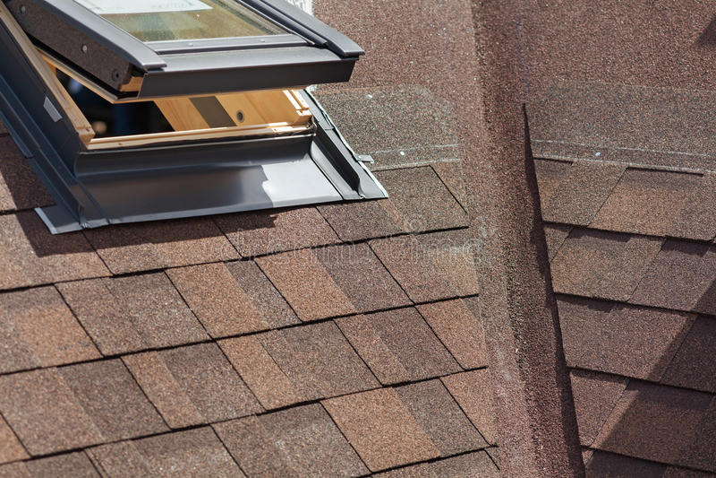Closeup av fönstertakfönstret på ett tak med Asphalt Shingles eller bitumentegelplattor under konstruktion arkivbilder