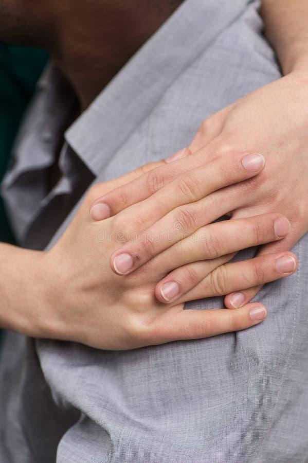 Closeup av flickahänder som kramar pojkvänskuldran royaltyfri foto