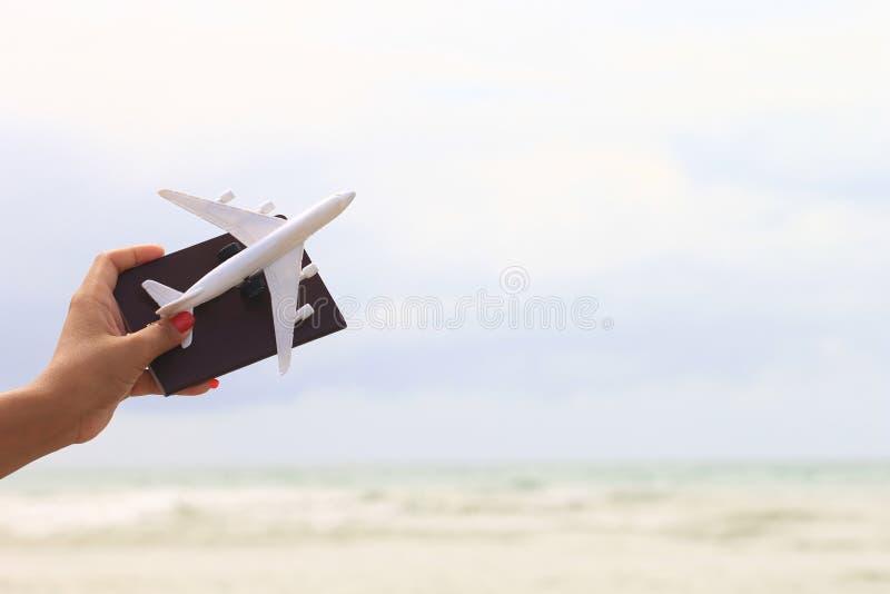 Closeup av flickainnehavflygplanet och pass på sommarnaturlandskapet av den vita sandstranden, loppbegrepp arkivbild
